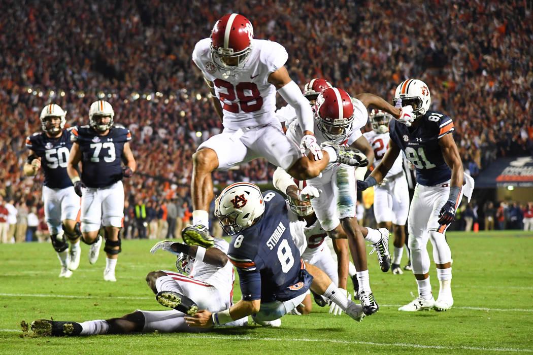 Nov 25, 2017; Auburn, AL, USA; Auburn Tigers quarterback Jarrett Stidham (8) scores a touchdown as Alabama Crimson Tide defensive back Anthony Averett (28) jumps over during the fourth quarter at  ...