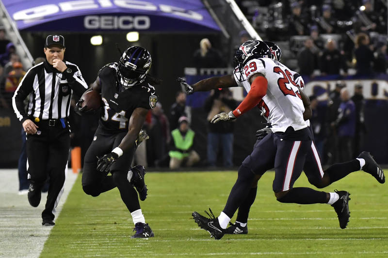 Nov 27, 2017; Baltimore, MD, USA; Baltimore Ravens running back Alex Collins (34) runs along the side line as Houston Texans safety Andre Hal (29) defends during the third quarter at M&T Bank  ...