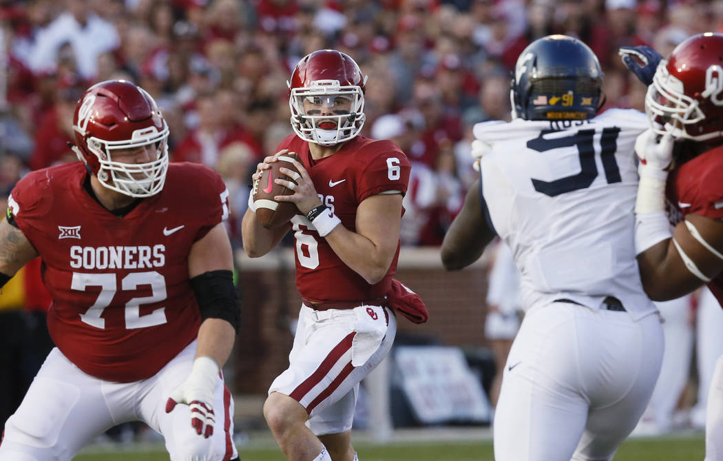 Oklahoma quarterback Baker Mayfield (6) prepares to pass in the second quarter of an NCAA college football game against West Virginia in Norman, Okla., Saturday, Nov. 25, 2017. (AP Photo/Sue Ogrocki)