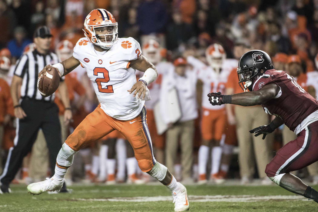 Clemson quarterback Kelly Bryant (2) eludes South Carolina linebacker Skai Moore (10) during the second half of an NCAA college football game Saturday, Nov. 25, 2017, in Columbia, S.C (AP Photo/Se ...