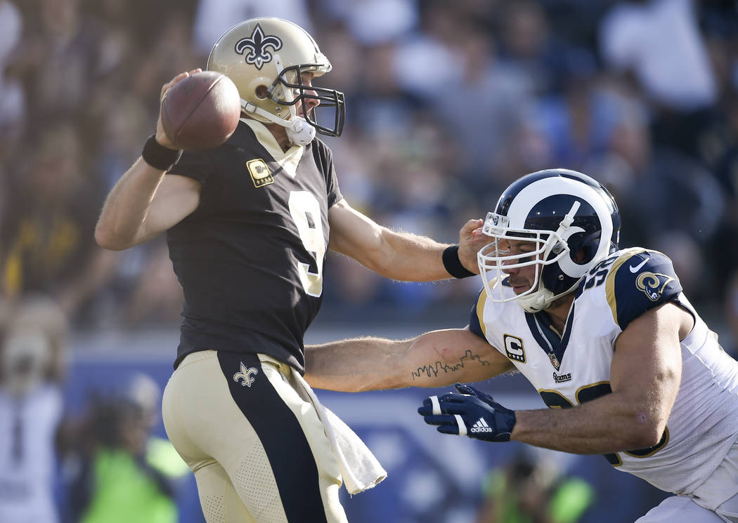 New Orleans Saints quarterback Drew Brees, left, attempts to avoid the rush by Los Angeles Rams linebacker Connor Barwin during the first half of an NFL football game Sunday, Nov. 26, 2017, in Los ...