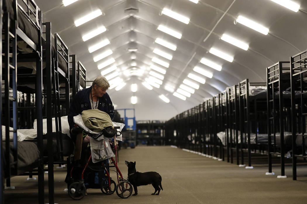 Verna Vasbinder prepares her her new bunk in the city's new Temporary Bridge Shelter for the homeless as her dog, Lucy Lui, looks on Friday, Dec. 1, 2017, in San Diego. (AP Photo/Gregory Bull)
