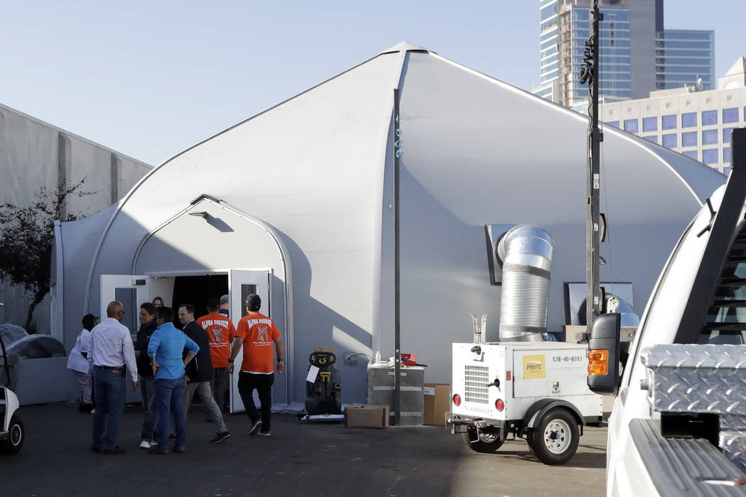 Crews work in front of the the city's new Temporary Bridge Shelter for the homeless Friday, Dec. 1, 2017, in San Diego.  (AP Photo/Gregory Bull)