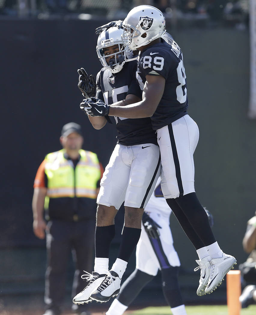 Oakland Raiders wide receiver Michael Crabtree, left, celebrates with wide receiver Amari Cooper after scoring a touchdown against the Baltimore Ravens during the first half of an NFL football gam ...