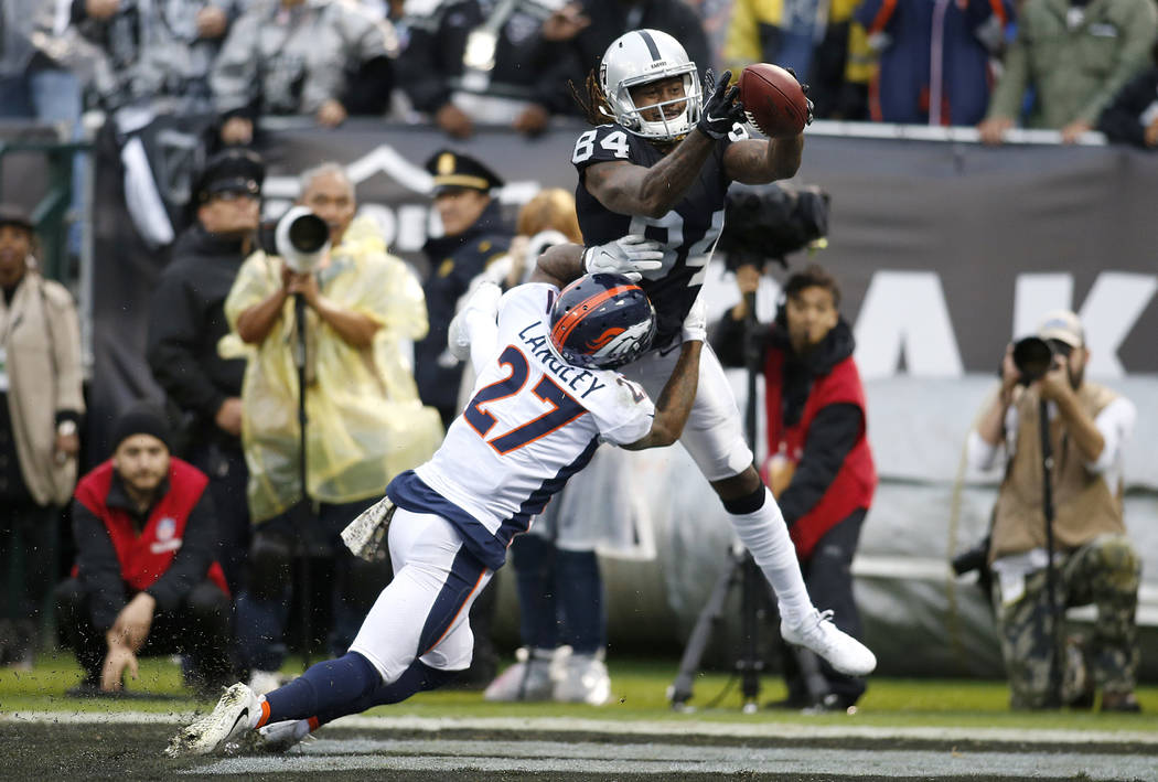 Broncos cornerback Brendan Langley (27) is called for pass interference on Oakland Raiders wide receiver Cordarrelle Patterson (84) during the first half of an NFL football game in Oakland, Calif. ...