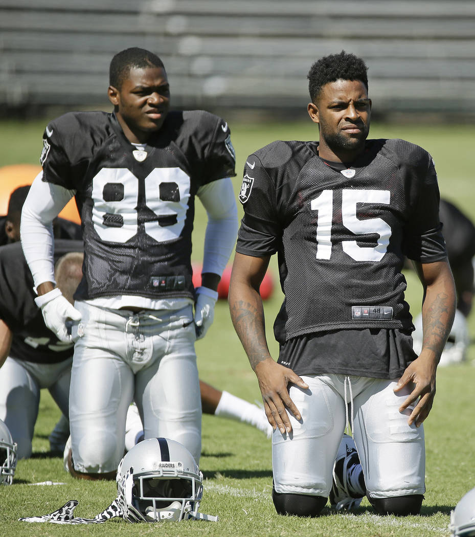 Oakland Raiders wide receivers Amari Cooper, left, and Michael Crabtree, right, stretch during their NFL football training camp Monday, Aug. 3, 2015, in Napa, Calif. (AP Photo/Eric Risberg)