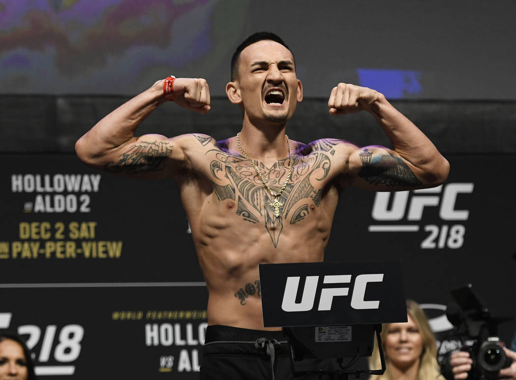 UFC featherweight champion Max Holloway reacts for the crowd during a weigh-in for a mixed martial arts match against Jose Aldo, Friday, Dec. 1, 2017, in Detroit. (AP Photo/Jose Juarez)