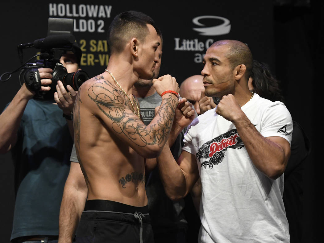 UFC featherweight champion Max Holloway, left, faces challenger Jose Aldo following weigh-ins for their mixed martial arts bout, Friday, Dec. 1, 2017, in Detroit. (AP Photo/Jose Juarez)