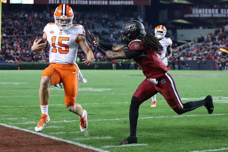 Nov 25, 2017; Columbia, SC, USA; Clemson Tigers quarterback Hunter Johnson (15) is chased out of bounds by South Carolina Gamecocks defensive back JaMarcus King (7) during the second half at Willi ...