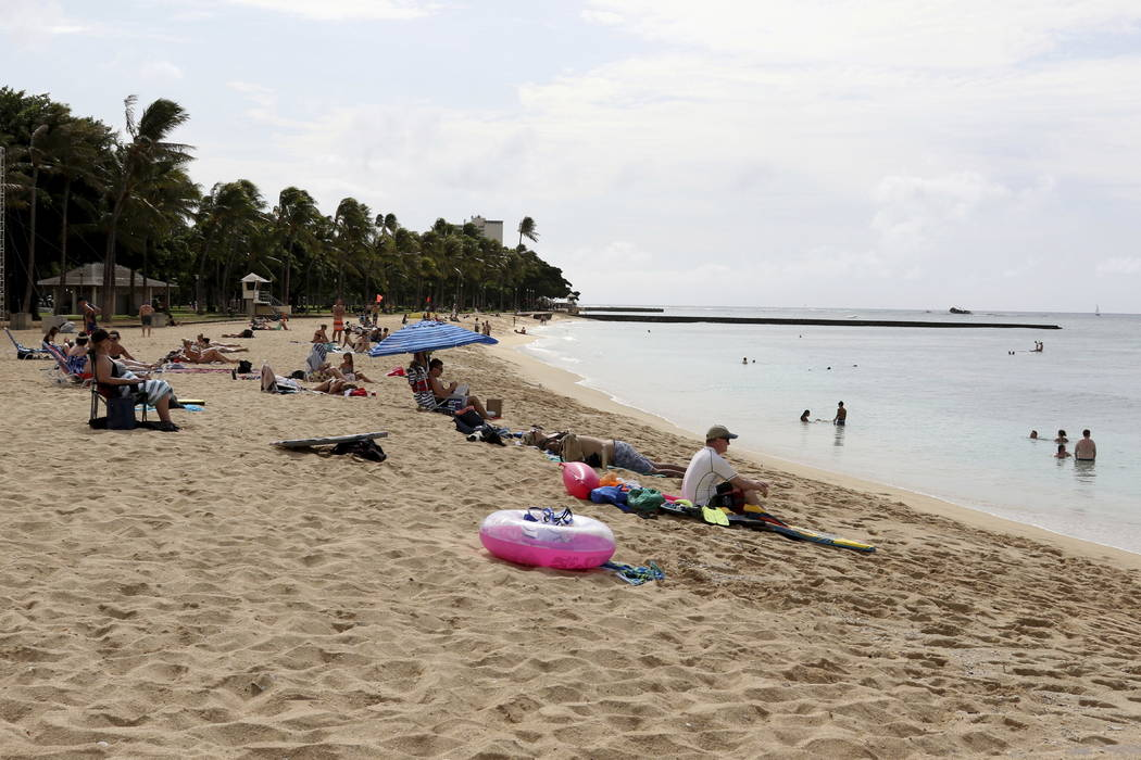 People sit on the beach and swim in the Waikiki area of Honolulu on Friday, Dec. 1, 2017.  (AP Photo/Caleb Jones)