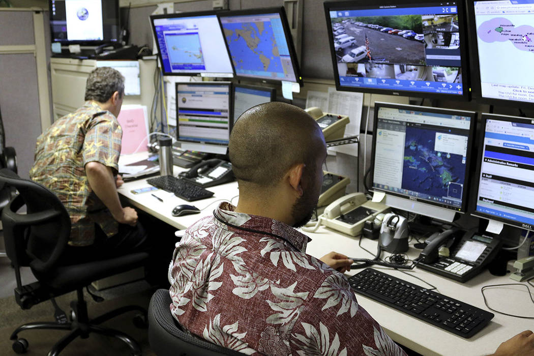 Hawaii Emergency Management Agency officials work at the department's command center in Honolulu on Friday, Dec. 1, 2017. (AP Photo/Caleb Jones)