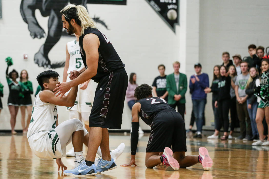 Palo Verde's Dylan Yoro (22), left, is helped up by Cimarron-Memorial's Noa Winquist (40), right, during the third quarter of a basketball game at Palo Verde High School in Las Vegas ...