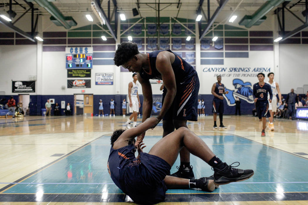 Legacyճ Cristian Pitts (3), left, is helped up by teammate Chris White (5), right, after falling during the third quarter of a basketball game against Canyon Springs at Canyon Springs High S ...