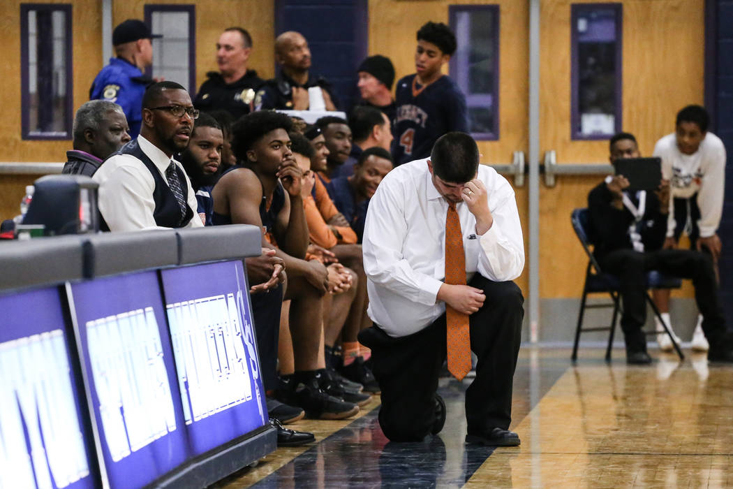 Legacy head coach Jack Tarango III kneels as he rubs his head following a Canyon Springs free-throw during the fourth quarter of a basketball game at Canyon Springs High School in North Las Vegas, ...