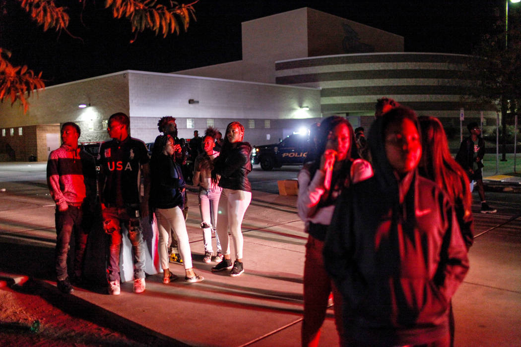 Students stand nearby after officers cleared an area using pepper spray to break up a fight following a basketball game at Canyon Springs High School in North Las Vegas, Friday, Dec. 8, 2017. Joel ...