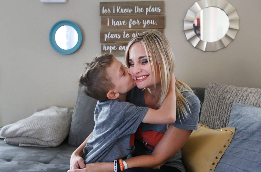 Christina Gruber, a Route 91 Harvest festival shooting survivor, receives a kiss on the cheek from her son Jake, 7, in her home in Las Vegas, Saturday, Dec. 2, 2017, before going to run the Vegas  ...