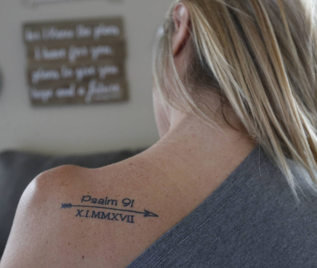Christina Gruber, a Route 91 Harvest festival shooting survivor, shows her tattoo in her home in Las Vegas, Saturday, Dec. 2, 2017, before going to run the Vegas Strong 5K/1M. Chitose Suzuki Las V ...