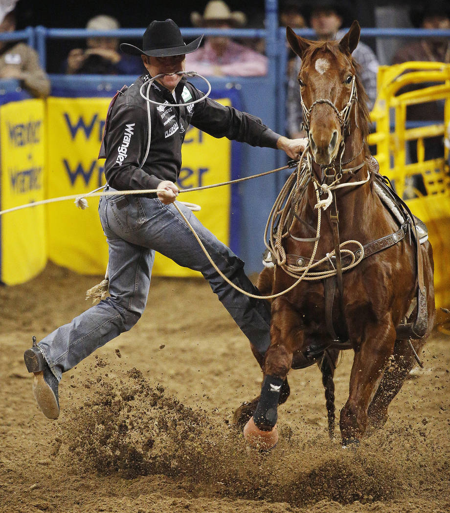 Trevor Brazile competes in the tie-down roping event for a first place time of 6.5 seconds during the eighth go-round of the National Finals Rodeo Thursday, Dec. 10, 2015, in Las Vegas. The time t ...