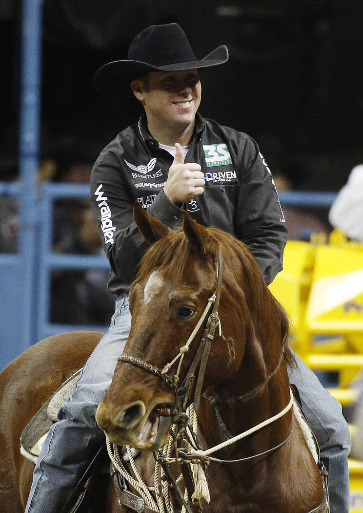 Trevor Brazile celebrates after competing in the tie-down roping event for a first place time of 6.5 seconds during the eighth go-round of the National Finals Rodeo, Thursday, Dec. 10, 2015, in La ...