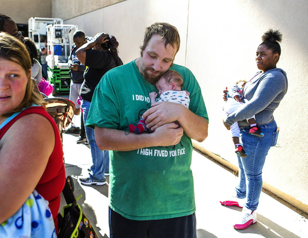 Angel Anguiano, holds his one-month old son Jeremiah while standing in line during Project Homeless Connect at Cashman Center on Tuesday, Nov., 15, 2016. His family is covered by Medicare. Jeff Sc ...