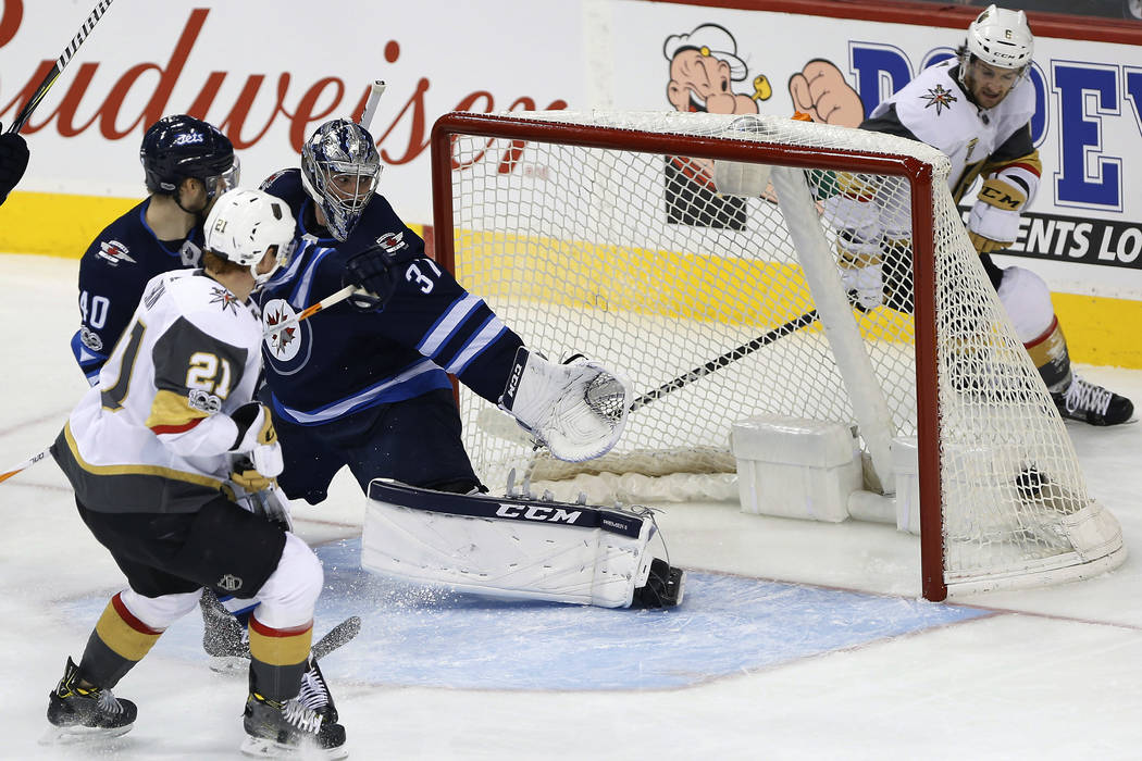 Winnipeg Jets goalie Connor Hellebuyck (37) looks on as Las Vegas Golden Knights' Cody Eakin's (21) shot hits the back of the net as Jets' Joel Armia (40) defends and Knights' Colin Miller (6) loo ...