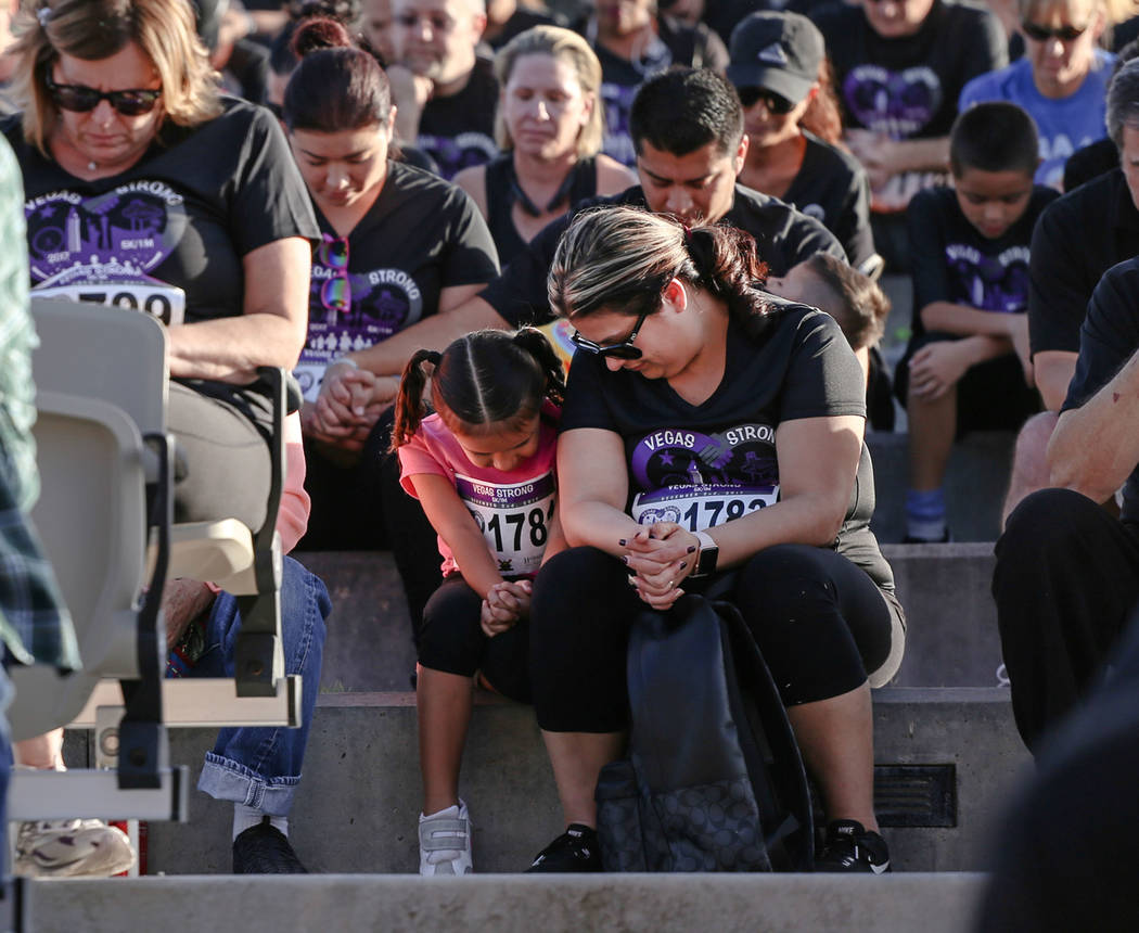 Faith Camacho, 6, left, sits next to her mother Erika Camacho, 34, right, both of Hesperia, Calif., during a moment of silence before the start of the Vegas Strong 5K/1M at Craig Ranch Region ...