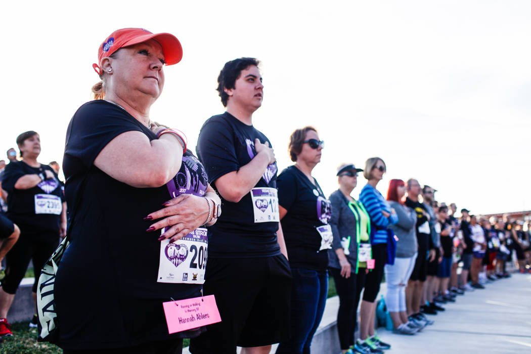 Ashley Nitz of Las Vegas, 55, a survivor of the Oct. 1 shooting, places her hand over her heart during the national anthem before the start of the Vegas Strong 5K/1M at Craig Ranch Regional Park i ...