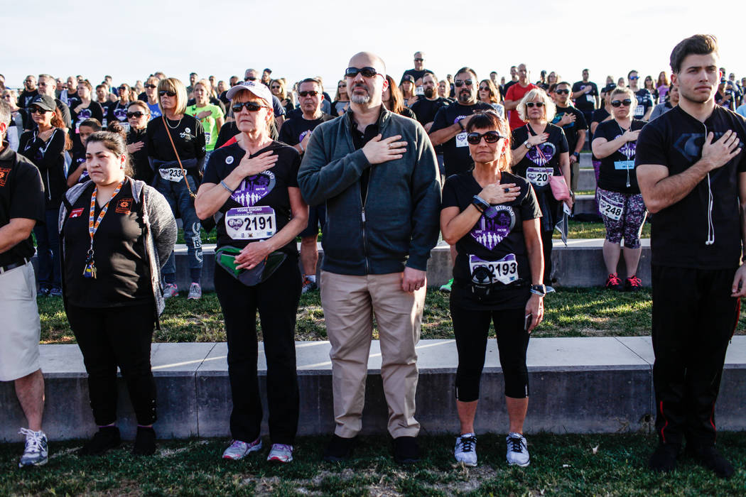 Karen Sanzare, 60, left, Vinny Sanzare, 51, center, both of Las Vegas, and Annette English of Seattle, Wash., 57, right, place their hands over their hearts during national anthem before the start ...