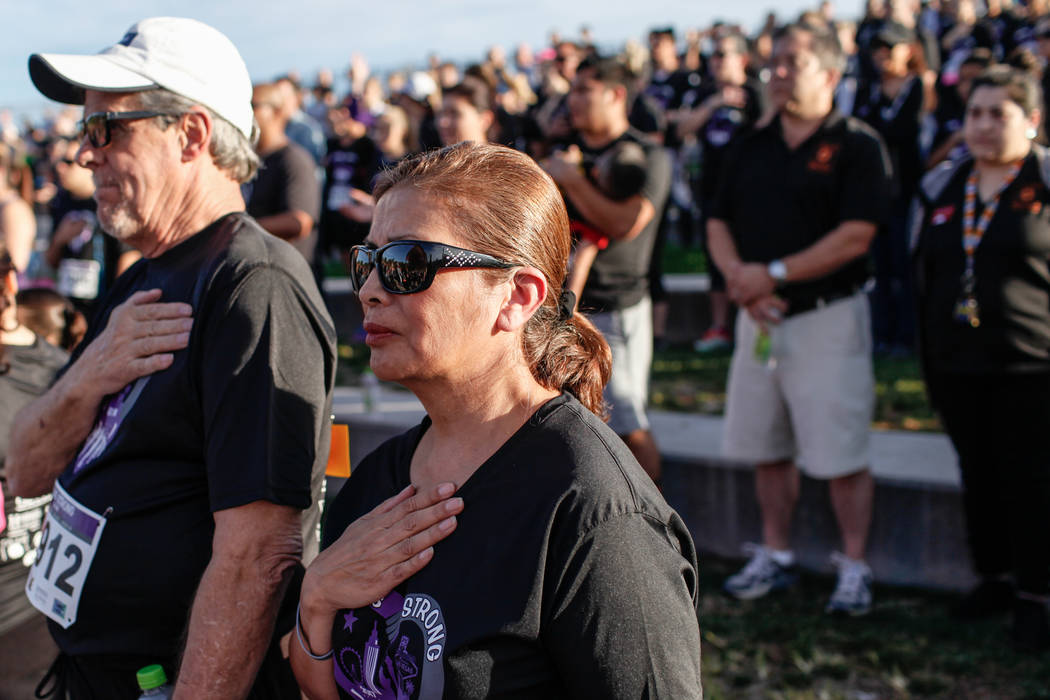 Chris Capler of Las Vegas, 57, right, places her hand over her heart during the national anthem before the start of the Vegas Strong 5K/1M at Craig Ranch Regional Park in North Las Vegas, Sat ...
