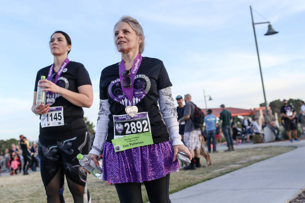 Kristine Johnson of St. George, Utah, 42, left, and Cathy Stuchell of Las Vegas, 61, right, watch as people finish the Vegas Strong 5K/1M at Craig Ranch Regional Park in North Las Vegas, Saturday, ...