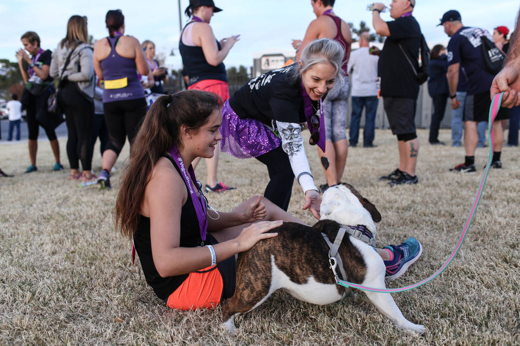 Celine Lucero-White of Kingman, Ariz., 17, left, and Cathy Stuchell of Las Vegas, 61, right, play with a dog after finishing  the Vegas Strong 5K/1M at Craig Ranch Regional Park in  ...