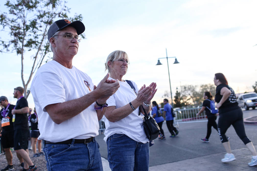 Dave Dalton, 59, left, and his wife Carol Dalton, 57, right, both of Concord, Mass., also both survivors of the Oct.1 shooting, applaud as runners complete the final stretch of  the Vega ...