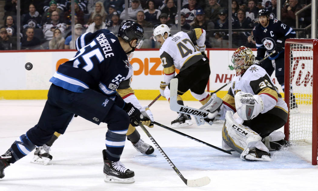 Dec 1, 2017; Winnipeg, Manitoba, CAN;  Vegas Golden Knights goalie Maxime Lagace (33) watches a lose puck bounce past Winnipeg Jets center Mark Scheifele (55) in second period play at Bell MTS Pla ...