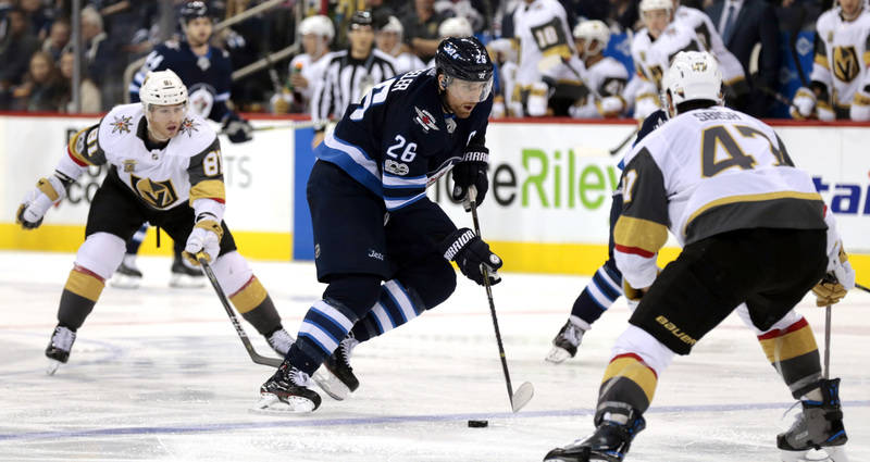 Dec 1, 2017; Winnipeg, Manitoba, CAN;  Winnipeg Jets right wing Blake Wheeler (26) skates throughout the neutral zone to Vegas Golden Knights defenseman Luca Sbisa (47) in second period action at  ...