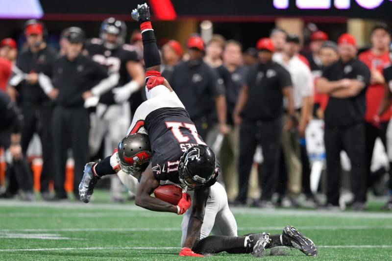 Nov 26, 2017; Atlanta, GA, USA; Tampa Bay Buccaneers safety Justin Evans (21) upends Atlanta Falcons wide receiver Julio Jones (11) during the second half at Mercedes-Benz Stadium. Mandatory Credi ...
