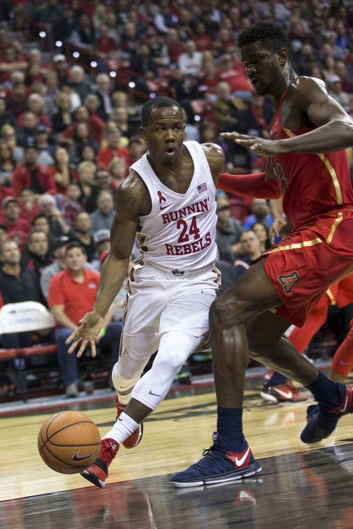 UNLV Rebels guard Jordan Johnson (24) dribbles the ball past Arizona Wildcats forward Deandre Ayton (13) during the first half of an NCAA college basketball game at Thomas & Mack Center in Las ...
