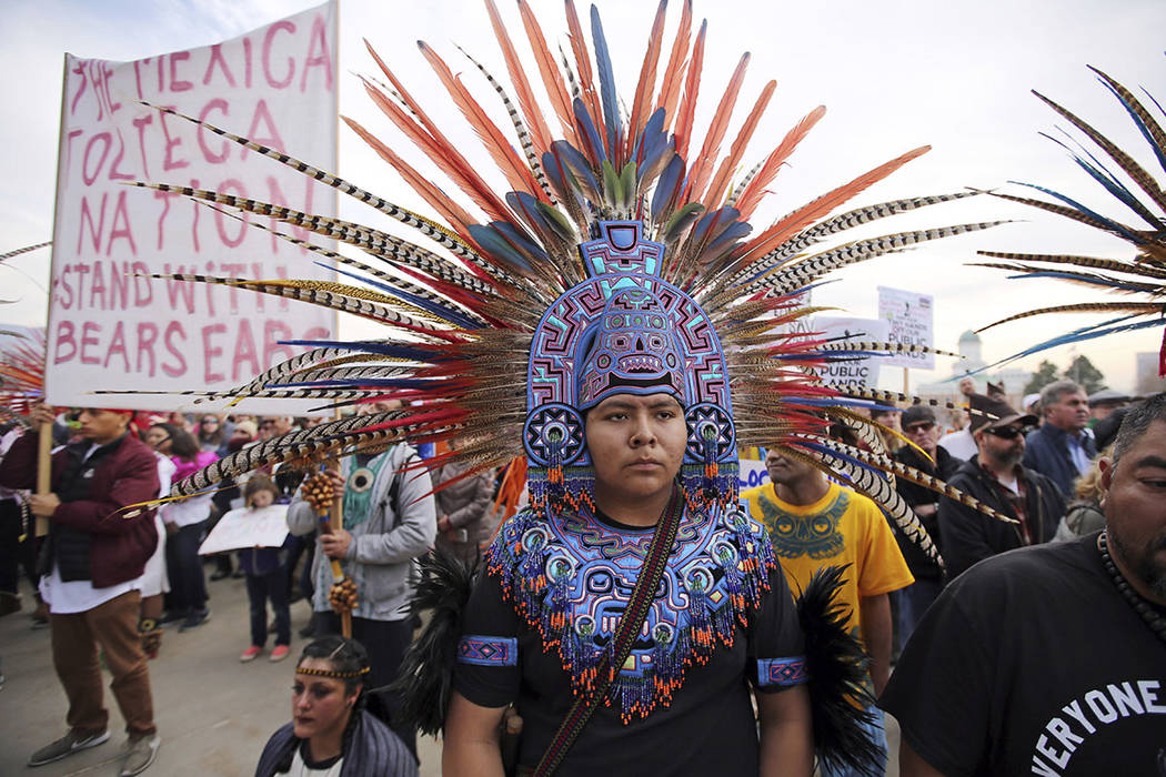 A supporter of the Bears Ears and Grand Staircase-Escalante National Monuments wears a colorful headdress during a rally Saturday, Dec. 2, 2017, in Salt Lake City. (AP Photo/Rick Bowmer)
