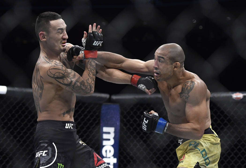 Max Holloway, left, is hit by Jose Aldo, of Brazil, during the first round of a UFC 218 featherweight mixed martial arts bout, early Sunday, Dec. 3, 2017, in Detroit. (AP Photo/Jose Juarez)