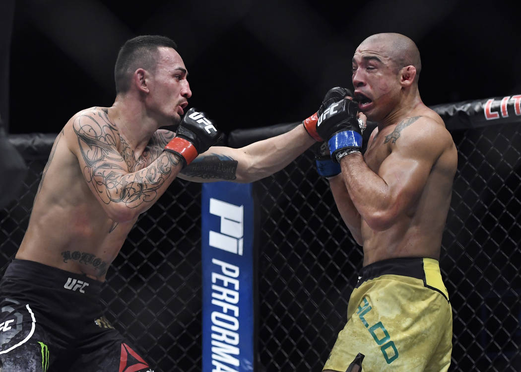 Max Holloway, left, punches Jose Aldo, of Brazil, during the third round of a UFC 218 featherweight mixed martial arts bout, early Sunday, Dec. 3, 2017, in Detroit.  (AP Photo/Jose Juarez)