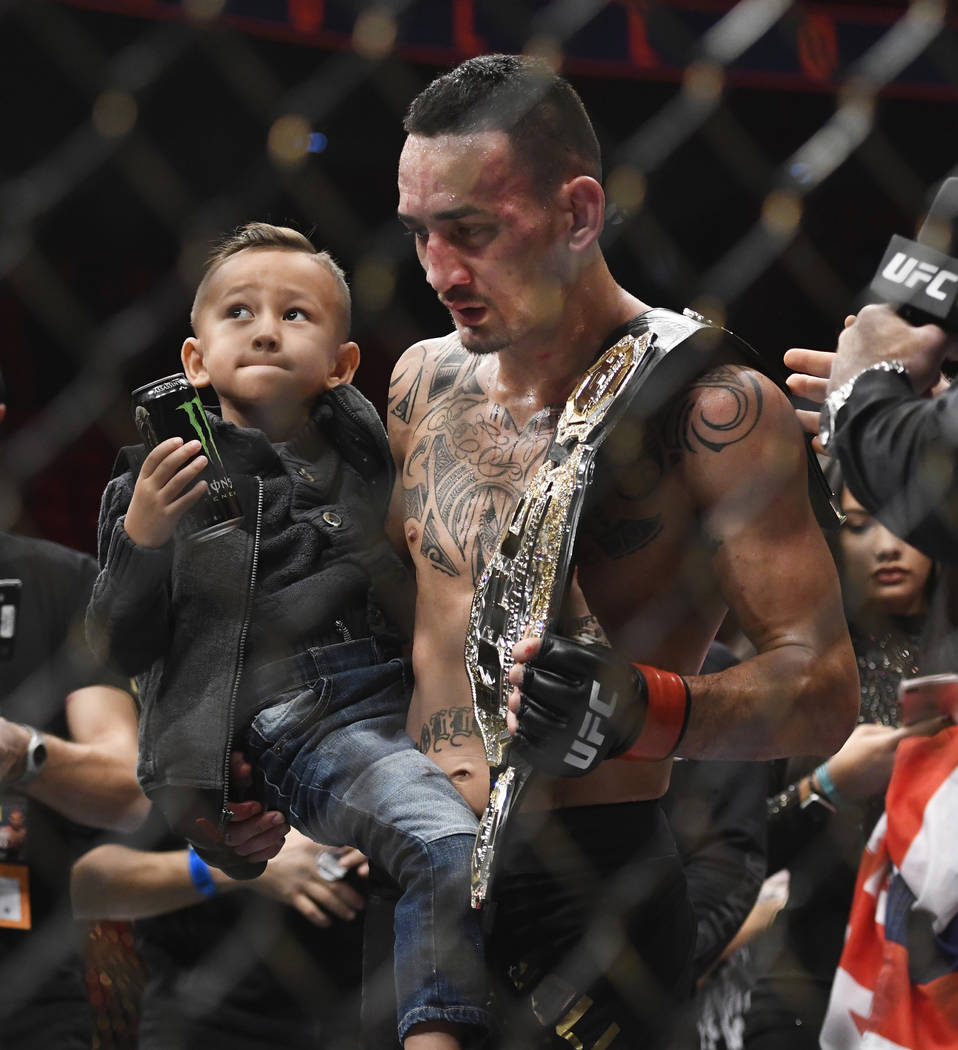 Max Holloway holds his son Rush, after Holloway defeated Jose Aldo, of Brazil, during a UFC 218 featherweight mixed martial arts bout, early Sunday, Dec. 3, 2017, in Detroit. (AP Photo/Jose Juarez)