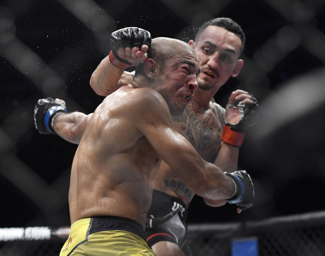 Max Holloway, right, punches Jose Aldo, of Brazil, during the third round of a UFC 218 featherweight mixed martial arts bout, early Sunday, Dec. 3, 2017, in Detroit. Holloway defeated Aldo by thir ...