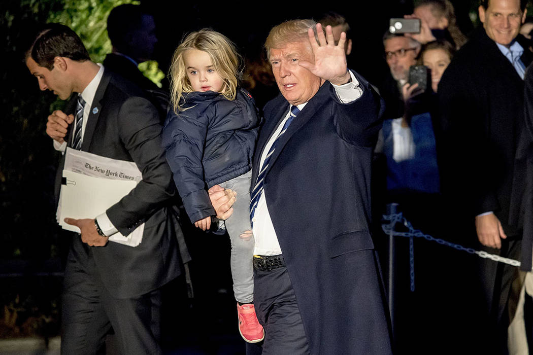 President Donald Trump holds a girl he picked up and waves to members of the media as he arrives on the South Lawn of the White House in Washington, Saturday, Dec. 2, 2017, after traveling to New  ...