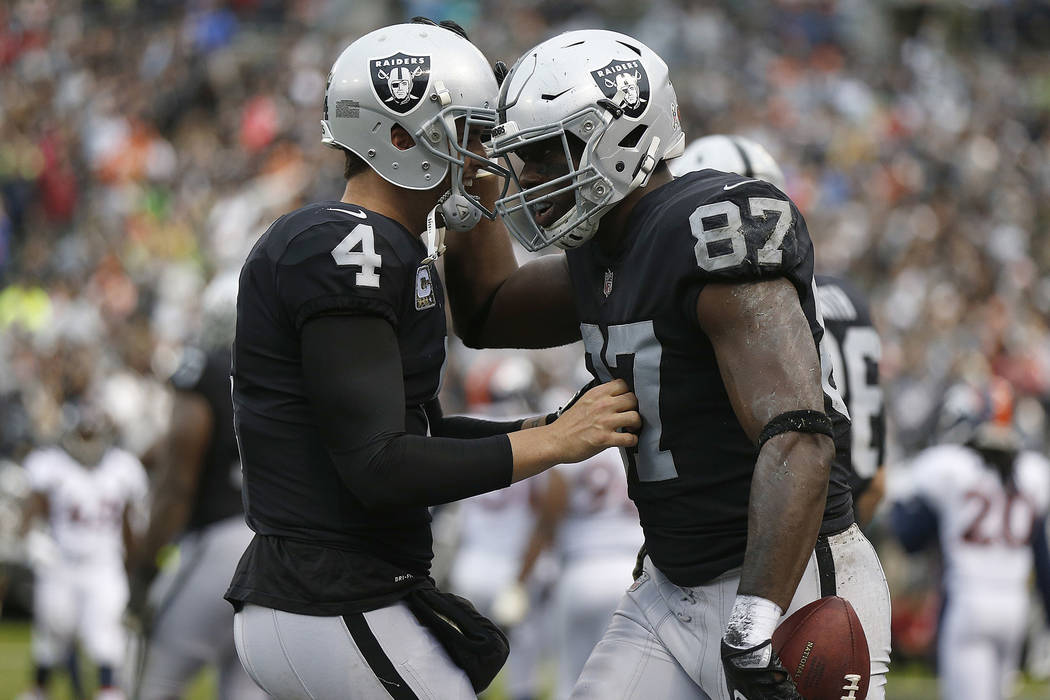 Oakland Raiders quarterback Derek Carr (4) and tight end Jared Cook (87) during an NFL football game against the Denver Broncos in Oakland, Calif., Sunday, Nov. 26, 2017. (AP Photo/D. Ross Cameron)