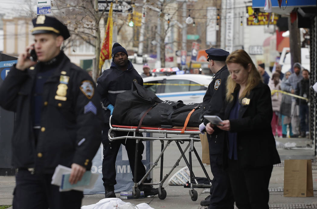 Police remove the body of a man following an incident, Sunday, Dec. 3, 2017, in the Queens borough of New York. Authorities are searching for a driver who struck a group of people, leaving at leas ...