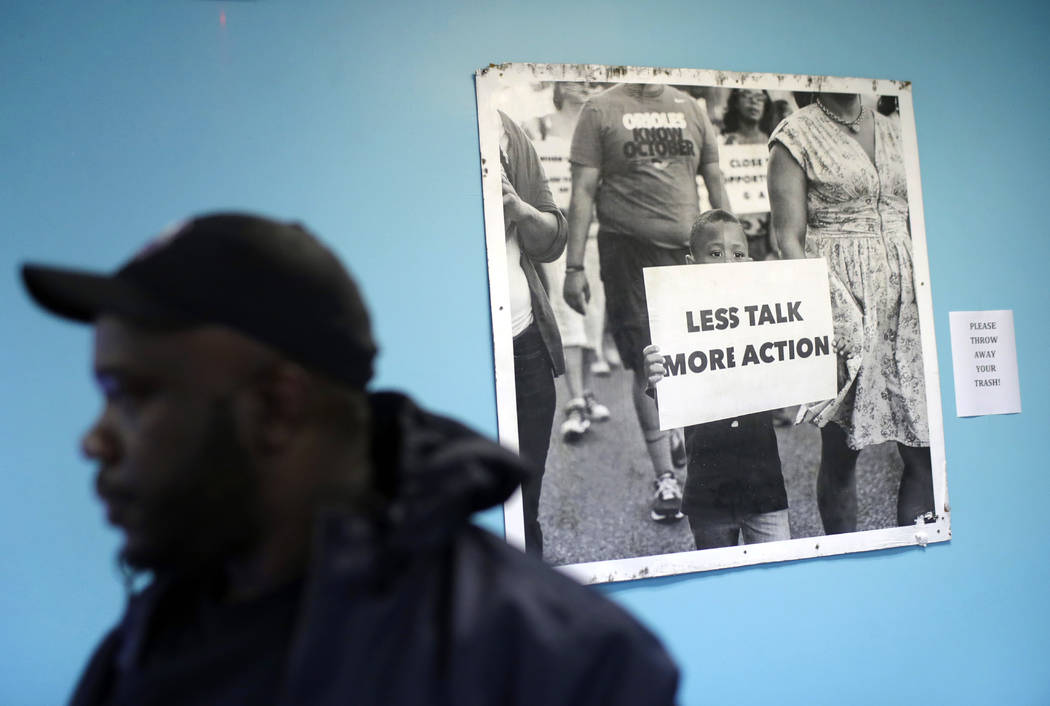 A photo from a Baltimore protest march hangs behind Kelvin Parker, a community outreach worker at U-TURNS, at a community center in Baltimore's Sandtown-Winchester neighborhood, March 2, 2017. Par ...