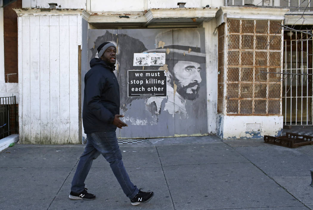Kelvin Parker, a community outreach worker at U-TURNS, walks past a blighted storefront in west Baltimore, March 3, 2017. Parker and his colleagues spend part of their shifts walking through a pub ...