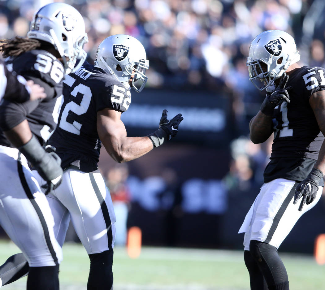 Oakland Raiders defensive end Khalil Mack (52) celebrates a fumble he recovered with outside linebacker Bruce Irvin (51) during the first half of a NFL game in Oakland, Calif., Sunday, Dec. 3, 201 ...