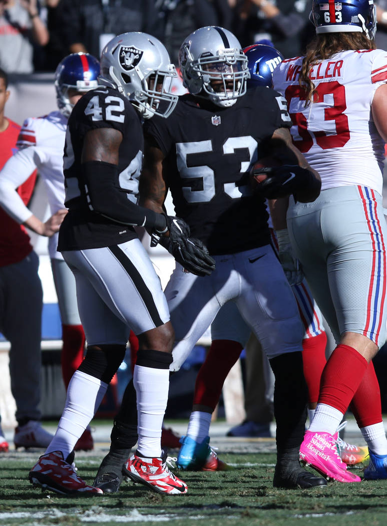 Oakland Raiders middle linebacker NaVorro Bowman (53) celebrates with strong safety Karl Joseph (42) after recovering a New York Giants fumble during the first half of a NFL game in Oakland, Calif ...