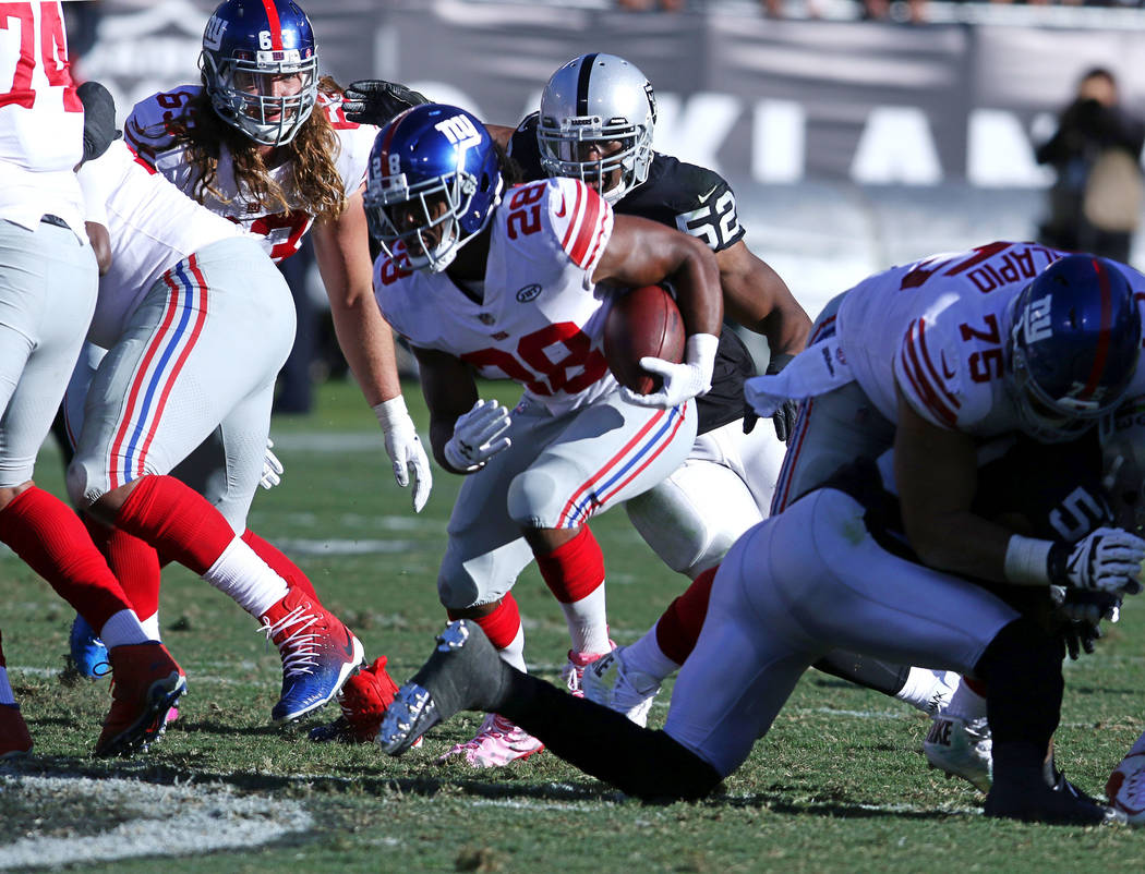 New York Giants running back Paul Perkins (28) runs with the football during the first half of a NFL game against the Oakland Raiders in Oakland, Calif., Sunday, Dec. 3, 2017. Heidi Fang Las Vegas ...