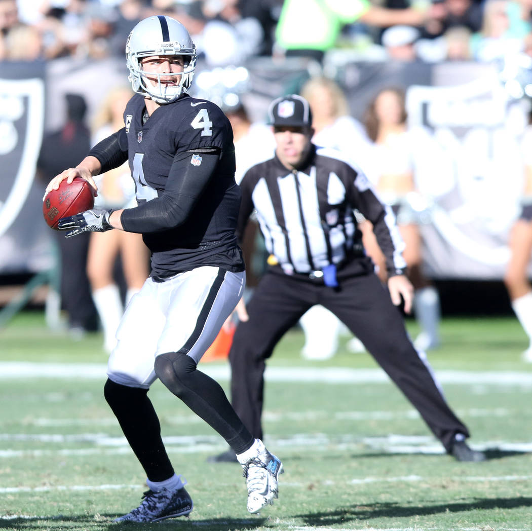 Oakland Raiders quarterback Derek Carr (4) prepares to throw the football against the New York Giants during the first half of a NFL game in Oakland, Calif., Sunday, Dec. 3, 2017. Heidi Fang Las V ...